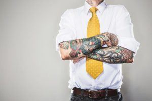 Decorative Image - A Man in a dress shirt and tie with folded tattooed arms