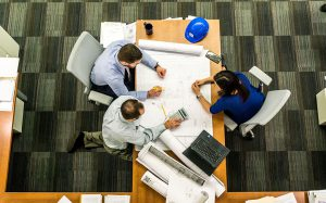 Decorative Image - Aerial view of 3 workers collaborating on work.
