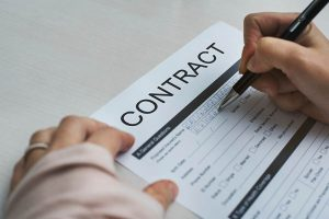Decorative Image - A person signing a contract