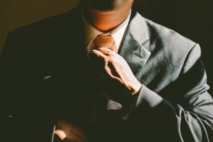Descriptive Image: Man adjusting necktie